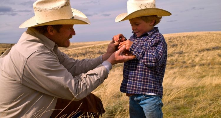 Cowboy father and son in field
